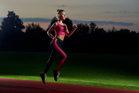 Side view of pretty and athletic girl in stylish black and pink sport wear running at night on stadium track. Woman preparing and training for first marathon. Concept of healthy and sport activity.