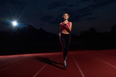 Positivity and happy young woman in sport wear running forward on track, looking and smiling at camera. Athletic girl with curly hair training, preparing alone to competition on stadium at night time.
