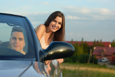 Front view of handsome man sitting in drivers seat in cabriolet and driving. Charming beautiful young woman with chestnut hair looking out car at camera and smiling. Couple traveling by car. Stock Photo