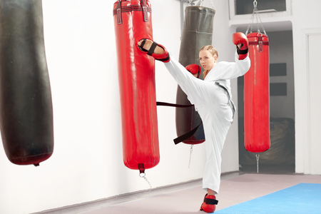 Young strong female wearing in white kimono and black belt working out karate raising leg and boxing heavy bag in gym. Sporty girl improving technique of fight at hard mixed martial arts training.
