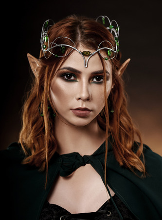 Close up of fantasy and mystical elf with red hair and brown eyes wearing tiara with emeralds. Wonderful and charming woman in dark green cloak tied around her neck looking at camera. Standard-Bild