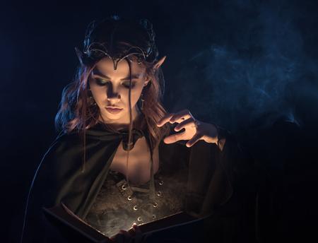 Cosecha de elfo de pelo rojo joven que aprende magia del libro de hechizos misteriosos. Bruja hermosa elegante en capa esmeralda que lanza un hechizo y hace niebla a su alrededor. Chica encantadora practicando habilidad mágica.