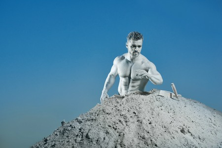View of well build man with muscles and silver skin looking, gesturing on instruments near. Atlas making himself from mountain on background of blue sky. Concept of motivation and working.