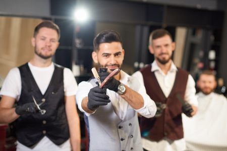 Selective focus of straight razor in hands of stylish hairdresser in vintage barber shop. Qualified male barbers in uniform and protective gloves looking at camera and posing at background.