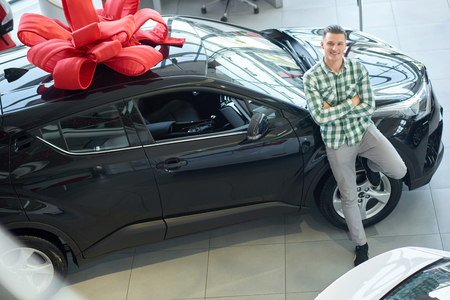 Young man in casual clothes leaning on big black car taken from above. Handsome blonde winner standing near his prize with crossing his hands on breast. Happy guy smiling near auto with bow on top. Reklamní fotografie
