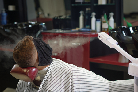 Young man with face covered with towel lying on chair in vintage barber shop while steam blowing from special equipment in face. Male client relaxing and resting during care procedure.