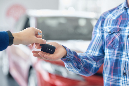 Close up of male hands and body in blue checkered shirt. Crop of hands when one person giving cars key to another. Man taking key from auto from his friend. On background standing red vehicle.