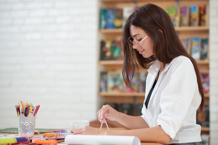 Charming young woman smiling and looking down. Female painter looking down and sitting at table with painters supplies. Beautiful girl wearing in spectacles and white shirt.
