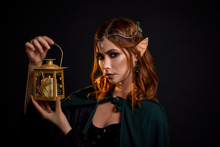 Portrait of charming mythical creature with red hair, in black dress and dark green cloak. Young beautiful elf with tiara on head holding in her hand golden lantern with white candle inside.