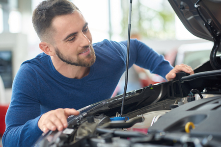 Close up of attractive happy man leaning on opened hood. Young customer in blue sweater choosing car in auto salon. Brunette driver with beard checking engine of new vehicle and squatting near it.