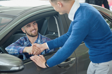 Menager leaning on front door and shaking hands with client after purchase. Young man in blue sweater helping his friend choosing vehicle. Brunette driver sitting in grey car and looking at brother.