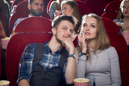 Cheerful couple having date in cinema. Smiling man talking it beautiful blonde girlfriend in gray. Cute pair watching interesting comedy and enjoying film together. Concept of free time of couple.