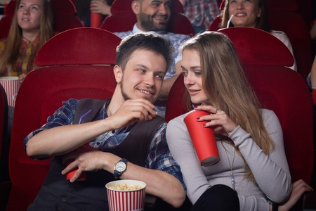 View from side of cute couple sitting together and looking each other at cinema hall. Pretty girlfriend and handsome boyfriend eating popcorn and enjoying funny comedy. Concept of free time.