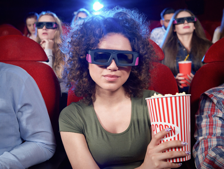 Portrait of attractive brunette looking at camera, smiling and posing during film in cinema hall. Pretty girl eating popcorn and watching funny interesting comedy. Concept of entertainment. Imagens