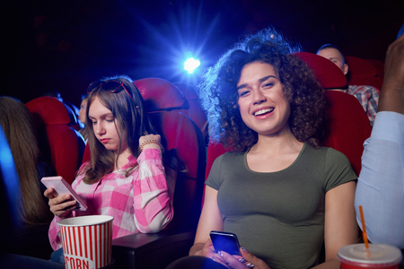 Portrait of attractive brunette looking at camera, smiling and posing during film in cinema hall. Pretty girl with curled hair watching funny interesting comedy. Concept of entertainment.