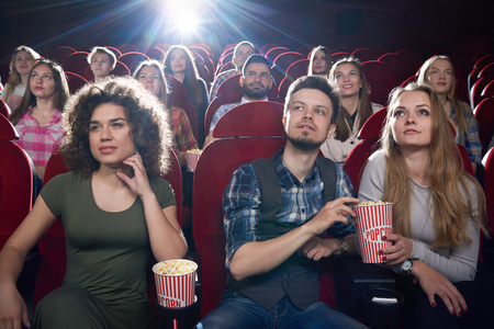 Front view of brunette girl and couple near sitting and hugging each other at cinema hall. Pretty girlfriend and handsome boyfriend eating popcorn and enjoying of interesting movie. Stock Photo