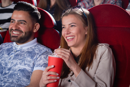 Positivity couple of blonde in gray and Arabian man in blue shirt drinking and smiling spending time in cinema. Students having fun, when looking at screen in modern cinema hall. Stock fotó