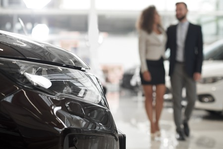 Husband and wife choosing expensive automobile in car showroom. Side view of auto headlight. Customers walking together in modern car dealership. Concept of vehicle business. Stock fotó