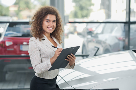 Female manager of car dealership standing in showroom and posing. Pretty woman with curly hair smiling, looking at camera. Car dealer holding black folder and pen.