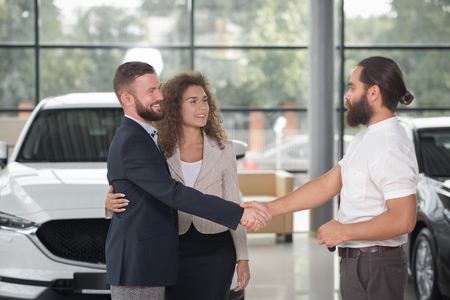 Couple making deal with manager of car dealership, buying automobile. Bearded man shaking hands with manager and looking at each other. Beautiful smiling woman holding hand round mans waist.