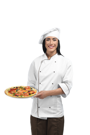 Close up of young happy and smiling woman posing at camera. Beautiful girl with black hair working as chef at restaurant and wearing special clothes. Pizzaiolo cooking her favourite pizza for guests.