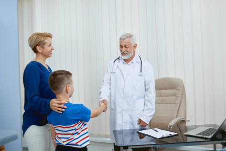 Portrait of mom and son on medical consultation in hospital. Professional doctor shaking hands with little boy working treating him. Woman listening diagnisis and presctiption after consultation.