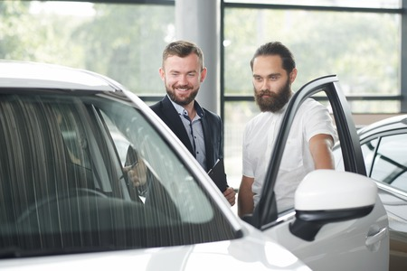 Car dealer showing car to customer. Brutal bearded man in white shirt looking at car, observing. Men standing near white automobile. Client looking for vehicle in car dealership. Stockfoto