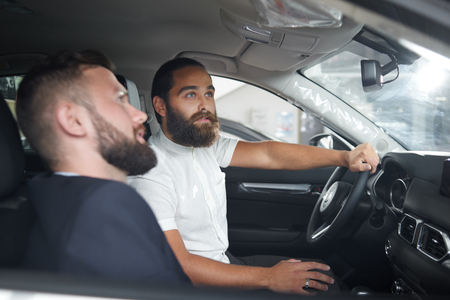 Car dealer showing to client car cabin. Handsome man in white shirt sitting on drivers seat, looking up and holding hand on steering wheel. Concept of car dealership and vehicle purchasing. Stock Photo