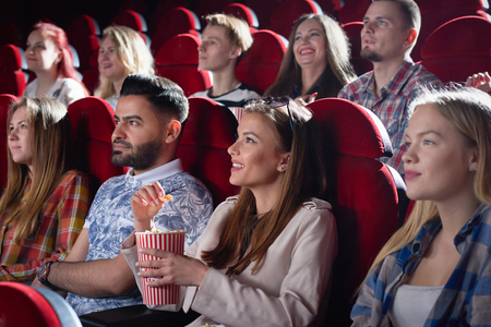 Side view of company of smiling beautiful woman watching movie in cinema hall. Blonde and brunette wearing red checkered shirt keeping popcorn. Concept of entertainment and movie time with friends. 版權商用圖片
