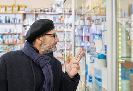 Old man in glasses looking at pharmacy shelf with medical products and pointing with fingers. Customer choosing medicines in drugstore. Man wearing in scarf, coat and male beret. Imagens