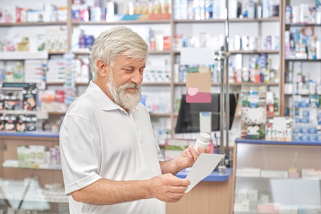 Cheerful old man standing in drugstore and looking at prescription paper in hand. Senior man having grey hair and beard, wearing in white t shirt. Pensioner choosing remedy for disease.