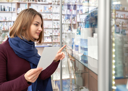 Beautiful woman with scarf on neck holding prescription paper and pointing with finger at pharmacy shelf. Female client of drugstore choosing medical products, medicines for health care. Imagens