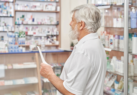 Senior man with grey hair and beard standing in drugstore with prescription in hand. Old man looking for medicines and remedy in chemists store. Pensioner looking at pharmacy shelves.