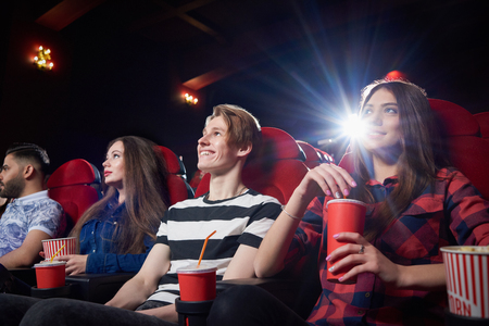 View from side of girl in red holding popcorn in red cup and watching intriguing movie in cinema. Pretty woman with friends expecting final of shocking film. Darkness modern cinema hall.