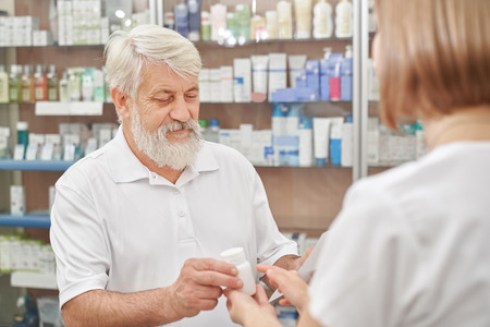 Pensioner looking at prescription and consulting with female pharmacist. Woman giving white bottle with pills. Old man buying medicines in drugstore. Specialist helping customer.