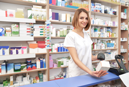 Beautiful woman wearing in white lab coat working in drugstore. Happy pharmacist standing at counter in pharmacy. Specialist smiling, looking at camera, scanning barcode of medicament with scanner.