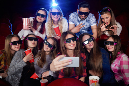 Positivity and funny group of students making photo on smartphone and taking selfie. Many pretty girls at camera during film in cinema hall taking self portrait wearing in 3d glasses. Concept of fun. Stock fotó