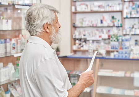 Bearded pensioner choosing medicines and medical products in chemists store. Senior man with grey hair wearing in white t shirt. Old man holding prescription paper in hand and standing in drugstore. Imagens