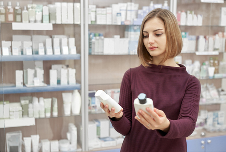Pharmacy customer standing in drugstore and choosing medical products. Woman looking at cosmetic white bottles. Consumer buying treatment for health care.