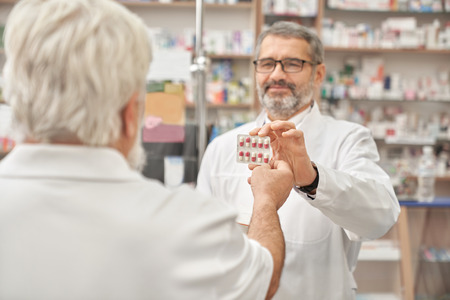 Happy pharmacist giving to customer blister pack of pills for health care. Elderly man taking tablets. Pensioner buying medicaments in drugstore. Concept of pharmaceutical industry.