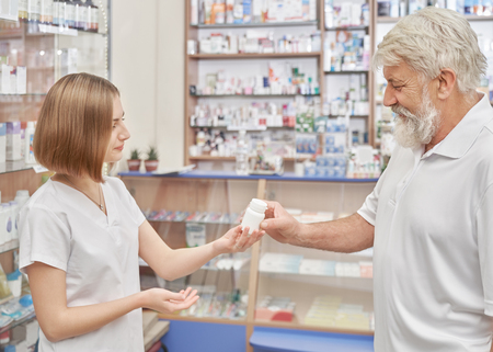 Female pharmacist helping pensioner with choice of medicaments in drugstore. Old man with grey hair consulting, taking white plastic pill bottle. Woman with chestnut hair wearing in white uniform.
