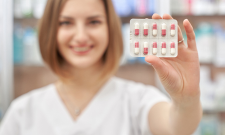 Close up of blister pack of pills, pharmacist holding in hand. Professional specialist showing medicines. Beautiful woman with short chestnut hair looking at camera, smiling.