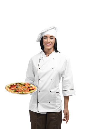 Portrait of happy young woman with black hair holding food and waiting for guests. Beautiful new chef of restaurant in working clothes with famous pizza. Happy and smiling pizzaiolo liking her job. Banque d'images