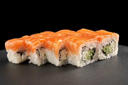Uramaki philadelphia roll covered with salmon, filled with cucumber and cream cheese. Philly rolls served on black stone slate plate.