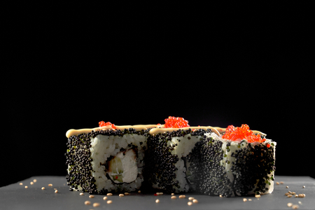 Philly sushi roll filled with cream cheese, fish and cucumber. Philadelphia maki topped with mayo and flying fish red roe, decorated with sesame. Stock Photo