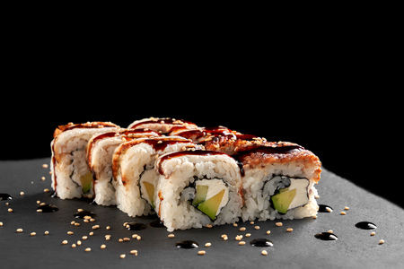 California rolls in sushi menu. Delicious sushi filled with cream cheese, avocado and smoked eel. Uramaki topped with unagi sauce, decorated with sesame. Reklamní fotografie - 118733991