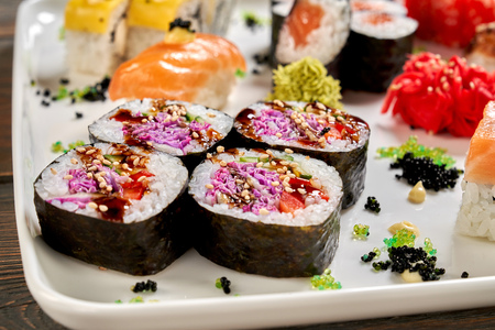 Vegaterian maki close up, on white plate with other kinds of sushi. Veggie rolls with vegetables, violet cabbage, cucumber, served with sause, pickled ginger and wasabi. Stock Photo