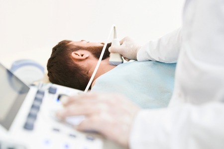 Hands of doctor using special equipment for ultrasound and sonography diagnostics. Doctor wearing in white medical gloves. Male patient lying, having his neck examined, lymph nodes.