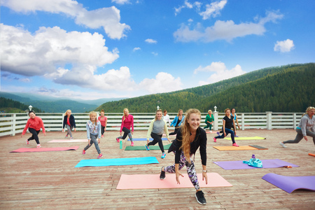 Sportive and healthy woman and girls practicing fitness during class on fresh air outside. Woman wearing in trendy sportswear. Female coach showing exercises for physical strength. Banco de Imagens