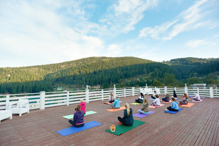 Group of people doing yoga together with coach on fresh air. People sitting in lotus pose observing amazing view of mountains. Women practicing on yoga mats, wearing in sportswear. Reklamní fotografie